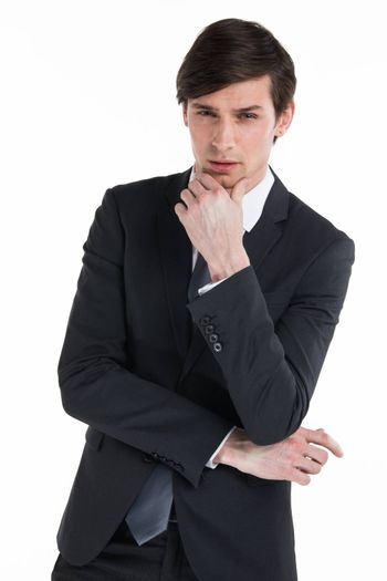 Frowning business man thinking over serious decision. Confident young man in formal suit touching chin