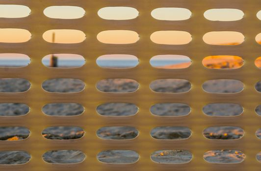 plastic fence pattern with the beach at sunset in the background, Belgian coast