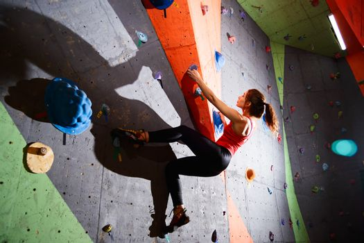 Young Active Woman Bouldering on the Colorful Artificial Rock in Climbing Gym. Extreme Sport and Indoor Climbing Concept