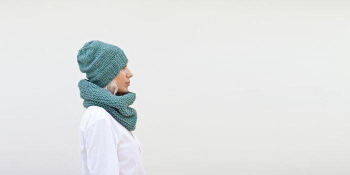 Pretty woman in warm turquoise knitted hat