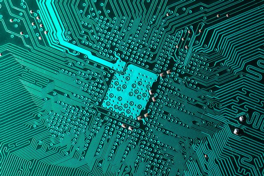 Close up photo of teal pcb printecd circuit board electric paths