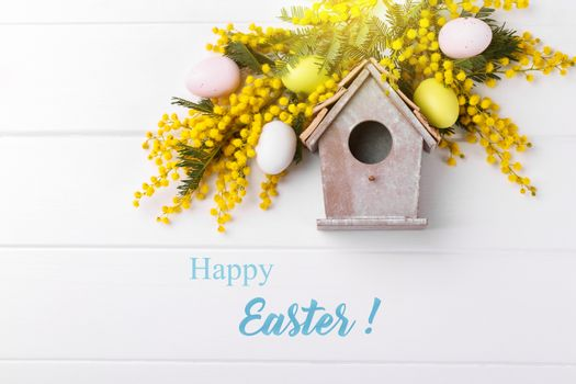 Bird house spring flowers mimosa and decorative easter eggs on white wooden bacground