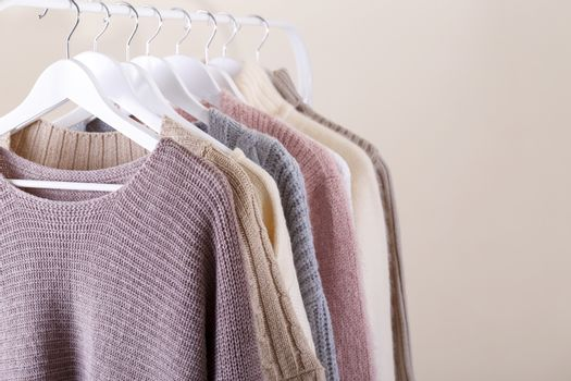 Warm knitted clothes hanging on a rack