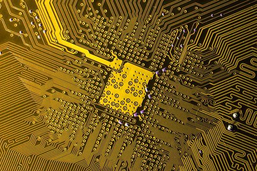 Close up photo of yellow pcb printecd circuit board electric paths