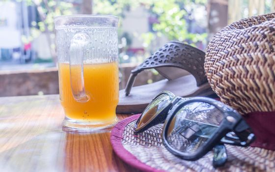 Modern women essential accessories for sunday weekend activities on wooden table. Sunglasses placed over Straw hat, flip flops, with a glass of lime juice with natural sunlight coming from window.
