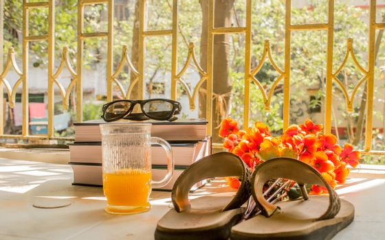 Modern women essential accessories for sunday weekend activities on wooden table. Sunglasses placed over Books, flip flops, a glass cocktail and flower bouquet with natural summer sunlight coming into