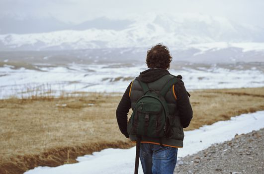 Man wearing backpack and looking at the winter mountains