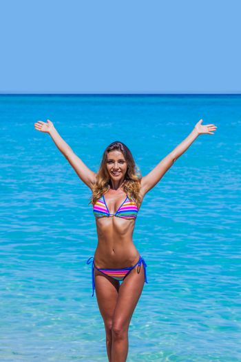 Beautiful happy girl walking from tropical sea with arms raised