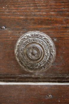 Ancient italian door handle on brown door