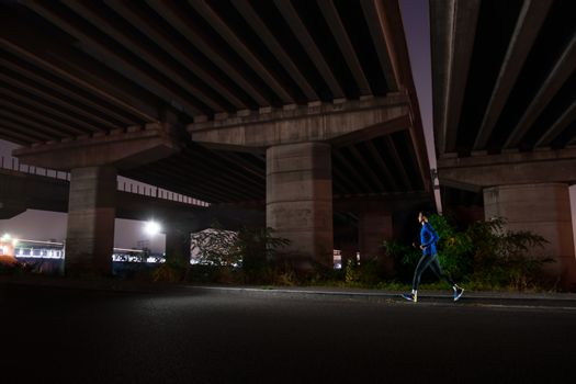Young Man in Blue Running at Night. Urban Running. Healthy Lifestyle and Sport Concept.