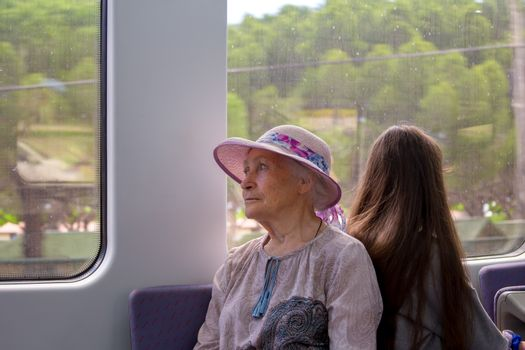 Beautiful gray-haired grandmother in a sunhat rides a commuter train and looks out the window.