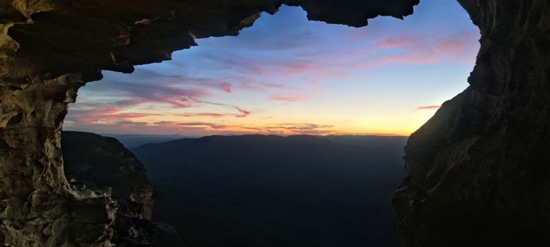 Mountain views to sunset from inside cliff cave