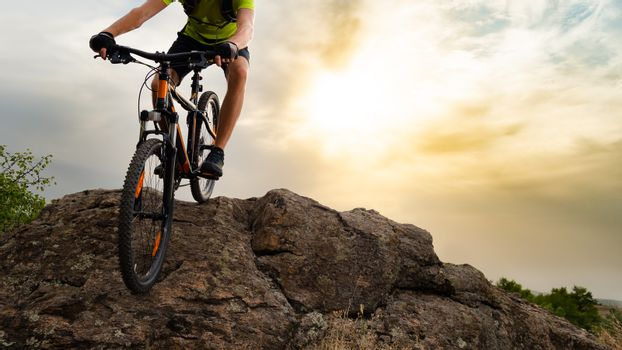 Cyclist Riding the Mountain Bike Down the Rock at Sunset. Extreme Sport and Enduro Biking Concept.