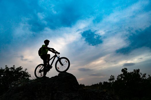 Silhouette of Cyclist with Mountain Bike on Rock at Sunset. Extreme Sports and Enduro Cycling Concept.