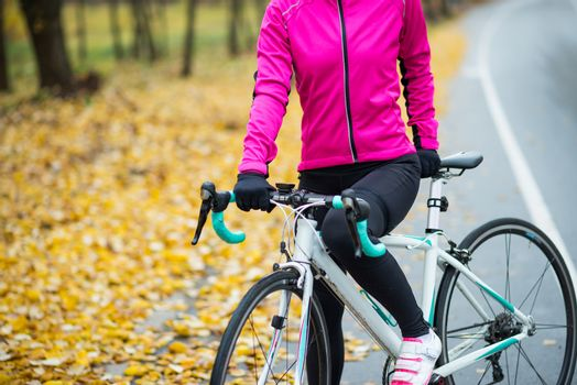 Female Cyclist in Bright Pink Jacket Resting with Road Bicycle in the Cold Sunny Autumn Day. Healthy Lifestyle Concept.