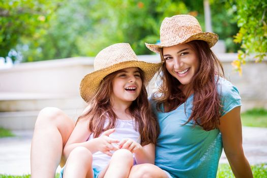 Portrait of happy young mother with cute cheerful daughter wearing the same straw hats playing outdoors, having fun on backyard