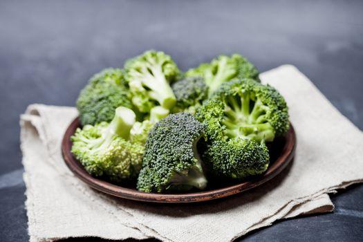 Fresh green organic broccoli in brown plate and linen napkin
