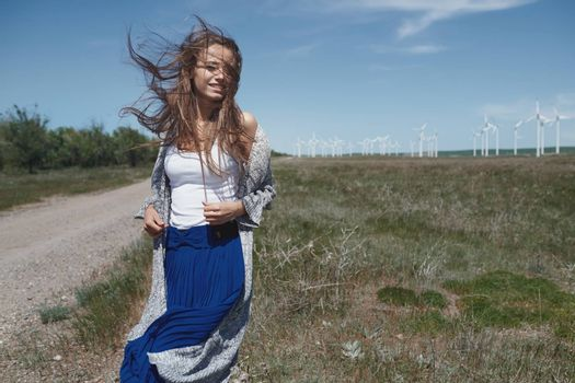 Woman with long tousled hair next to the wind turbine with the wind blowing
