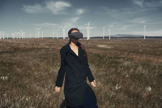 Woman wearing VR headset at the field next to the wind turbines