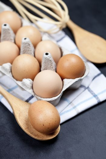 Eggs and kitchen utensil closeup on backboard background.