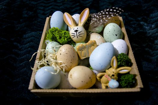 Easter bunny with moss grass and colorful eggs in a cardboard box