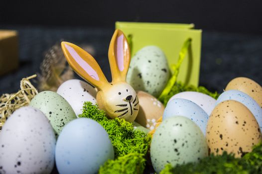 Small Easter bunny peeking from gift bag with colorful easter eggs and some grass.