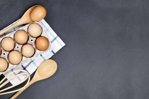 Fresh eggs and kitchen utensil on backboard background.