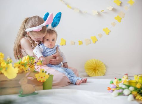 Loving cute girl and her little brother wearing bunny ears in Easter decor