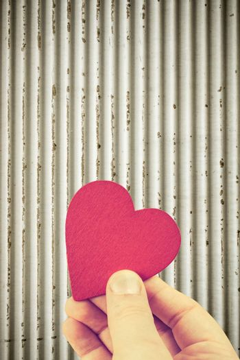 Red heart shaped object in hand as love concept