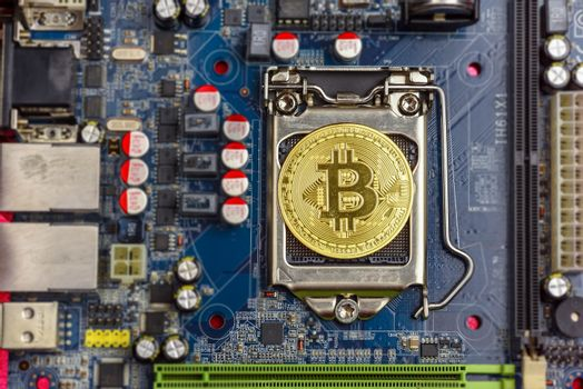 Top view of golden bit coin on computer mother board