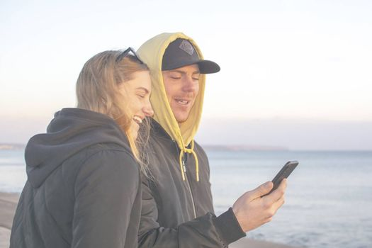 Handsome young natural and casual looking couple with hood jackets black and yellow watch sunset and photographing with smartphone on a beach.