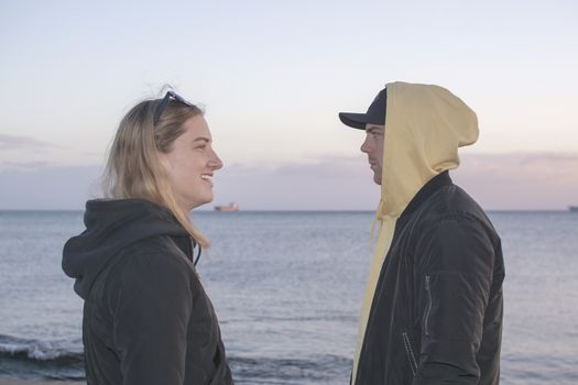 Handsome young natural and casual looking couple with hood jackets watch each other in profile at sunset on a beach.