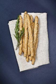 Italian grissini or salted bread sticks on linen napkin on black