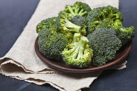 Fresh green organic broccoli in brown plate and linen napkin.