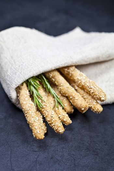 Italian grissini or salted bread sticks with rosemary herb on li