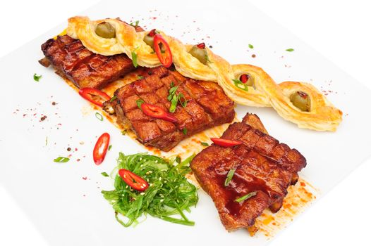 grilled pork ribs with bread pigtail and seaweed, served on plate, isolated on white