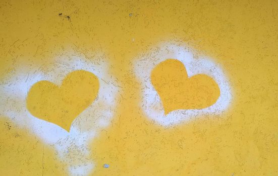 Silhouettes of two hearts on a yellow concrete wall. Close-up.