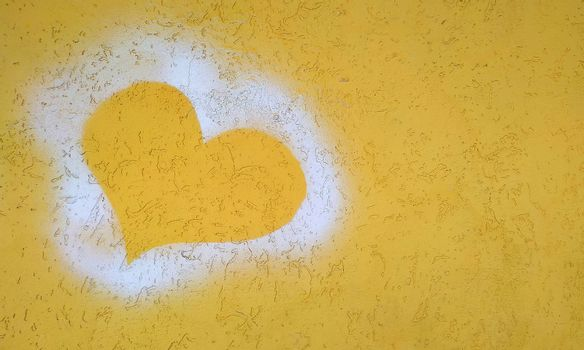Silhouette of the heart on the yellow plaster wall. Close-up.