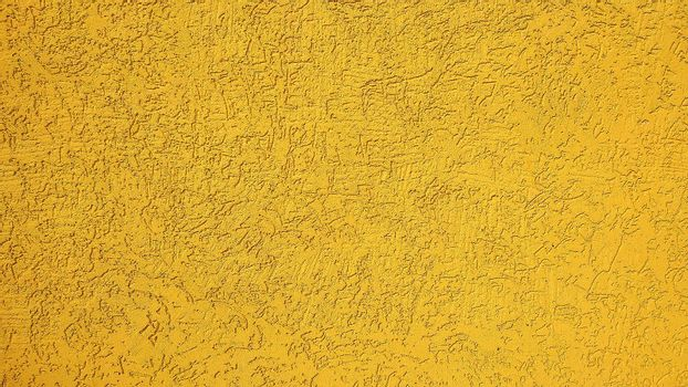 Plaster wall painted in yellow paint. Close-up.