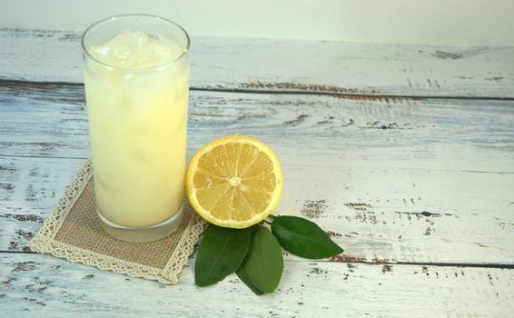 A glass cup with a refreshing juice and ice, on a textile stand and cut half of a lemon with leaves lies on a white wooden table. Close-up.