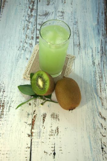A glass cup with a refreshing juice and ice, on a textile stand, whole and sliced half of kiwi with leaves lying on a white wooden table. Close-up.