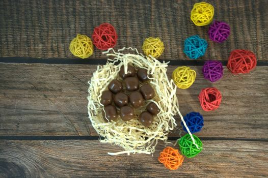 A nest of straw with chocolates and multicolored decorative balls on a wooden table. Close-up.