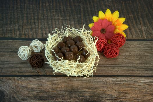 Round chocolates in a nest of straw, multicolored decorative balls and flower buds on a wooden table. Close-up.