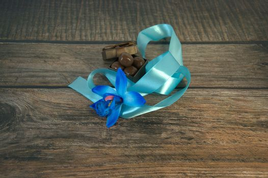 A box of chocolates, a blue ribbon, a bud of blue orchid and decorative balls on a wooden table. Close-up.