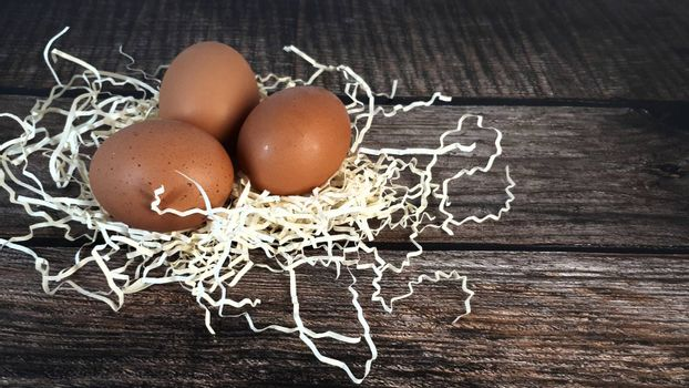 Three chicken eggs in a nest of straw on a wooden table. Close-up.
