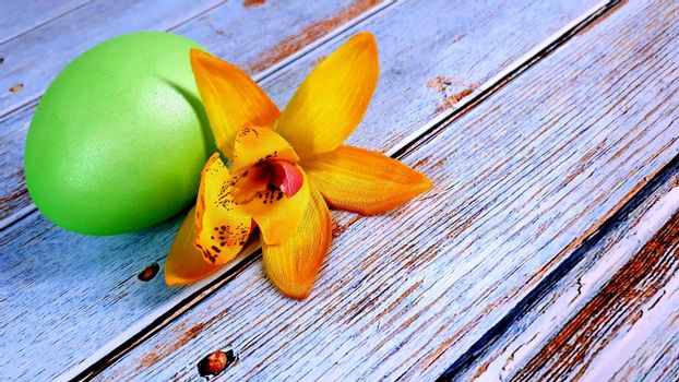 A green Easter egg and a flower are lying on a wooden table. Close-up.