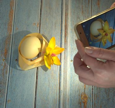 Female hands holding a smartphone photographing an Easter composition with an egg and a ribbon on a wooden table. Close-up.
