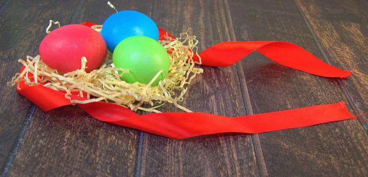 Painted Easter eggs in a nest of straw on a scarlet ribbon lie on a wooden table. Close-up.