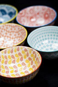 Five colorful empty ceramic bowls.