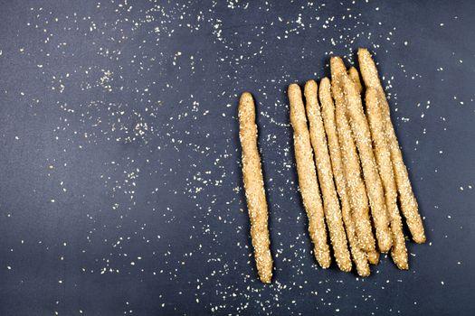 Italian grissini bread sticks with sesame seeds on black board b
